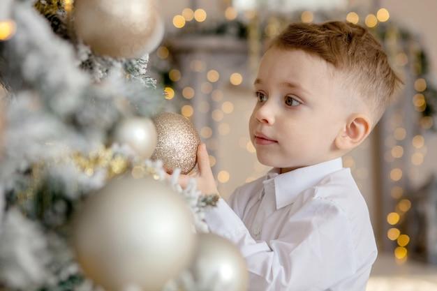 Il ragazzino decora un albero di natale per natale Foto Premium