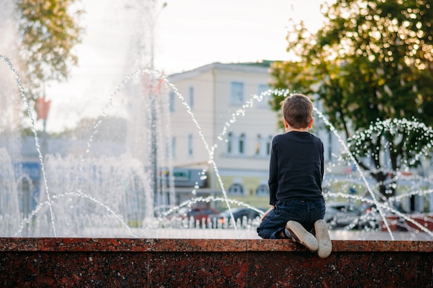 Il ragazzino esamina una fontana la sera soleggiata Foto Premium
