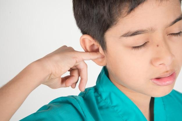 Il ragazzino ha mal di orecchio qualcosa bloccato nell'orecchio Foto Premium