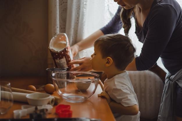 Il ragazzino in cucina aiuta la mamma a cucinare. il bambino è coinvolto nella cottura. Foto Gratuite