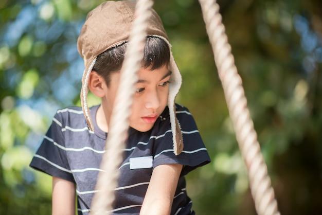 Il ragazzino si siede sull'oscillazione da solo con triste Foto Premium