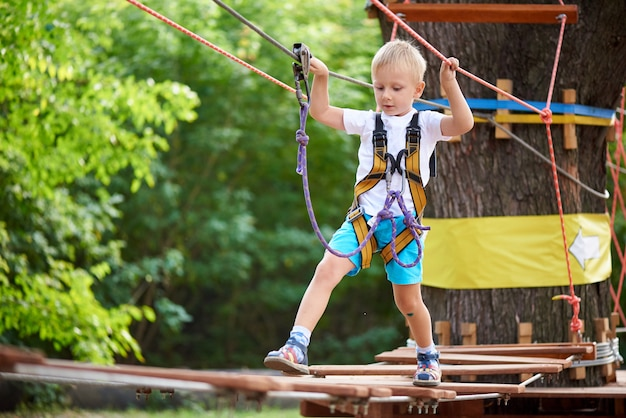 Il ragazzino supera un ostacolo in un parco di divertimenti Foto Premium