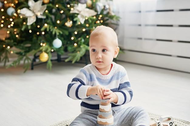 Il ragazzino sveglio sta giocando con il treno di legno del giocattolo, l'automobile del giocattolo, la piramide ed i cubi, imparanti il concetto di sviluppo. sviluppo delle capacità motorie, dell'immaginazione e del pensiero logico dei bambini Foto Premium