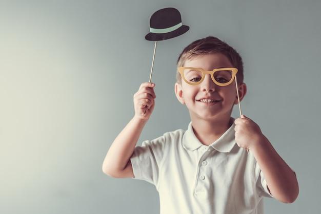 Il ragazzino sveglio sta tenendo un cappello e gli occhiali di carta. Foto Premium