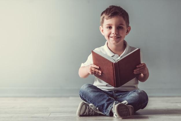 Il ragazzino sveglio sta tenendo un libro, sta esaminando la macchina fotografica. Foto Premium