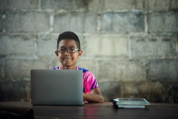 Il ragazzo asiatico che per mezzo del computer portatile sulla tabella, ritorna allo shcool Foto Gratuite