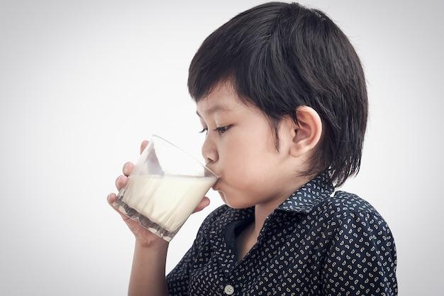 Il ragazzo asiatico sta bevendo un bicchiere di latte Foto Gratuite
