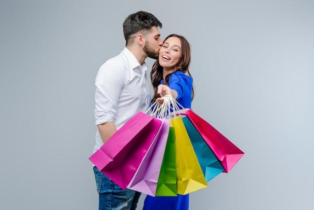 Il ragazzo bacia la ragazza con i sacchetti della spesa variopinti Foto Premium