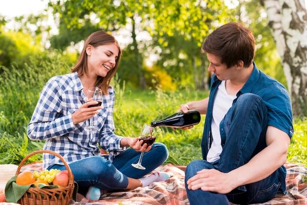 Il ragazzo che riempie gli occhiali ha tenuto dalla ragazza con vino Foto Gratuite
