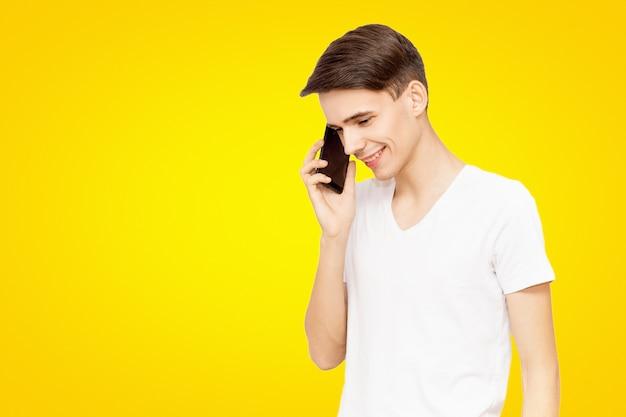 Il Ragazzo Con La Maglietta Bianca Parla Al Telefono Su Uno Sfondo