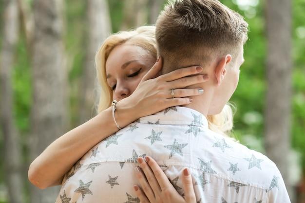 Il ragazzo con la ragazza abbraccia e bacia. un appuntamento romantico in una pineta, ama la coppia di una coppia adorabile Foto Premium