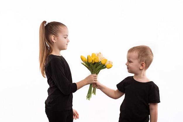 Il ragazzo dà una ragazza ai fiori Foto Premium