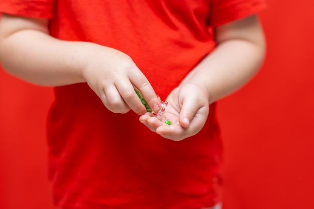 Il ragazzo del bambino versa le pillole dalla latta nella mano Foto Premium