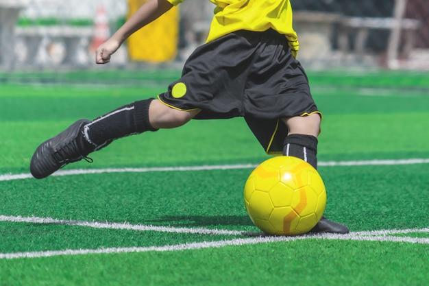 Il ragazzo di calcio si sta allenando calciare la palla nel campo di allenamento di calcio Foto Premium