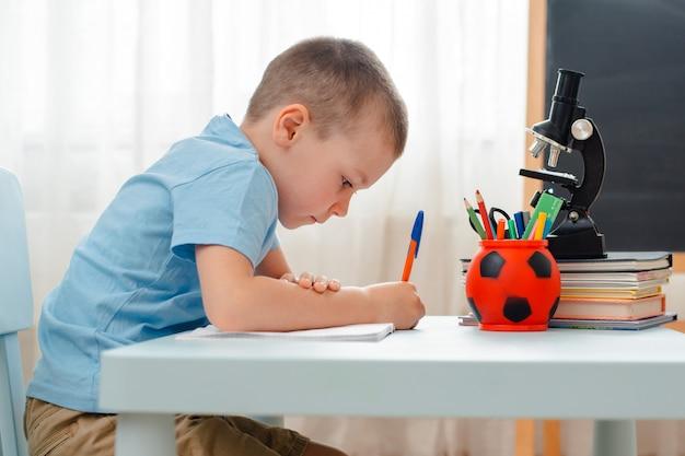 Il ragazzo di scuola che si siede a casa lo scrittorio di menzogne dell'aula ha riempito di materiale di addestramento dei libri lo scolaro che dorme annoiato pigro Foto Premium