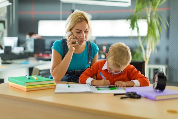 Il ragazzo e la donna svegli si siedono allo scrittorio nell'ufficio Foto Premium