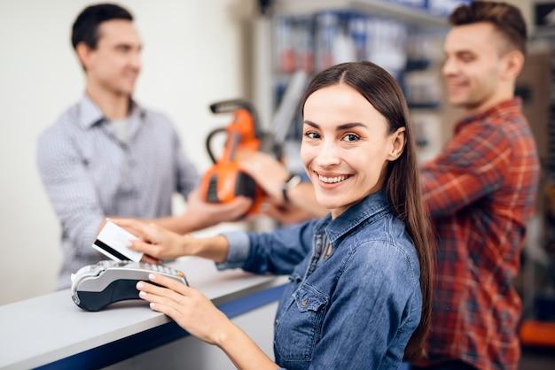 Il ragazzo e la ragazza pagano per l'acquisto di una motosega. Foto Premium