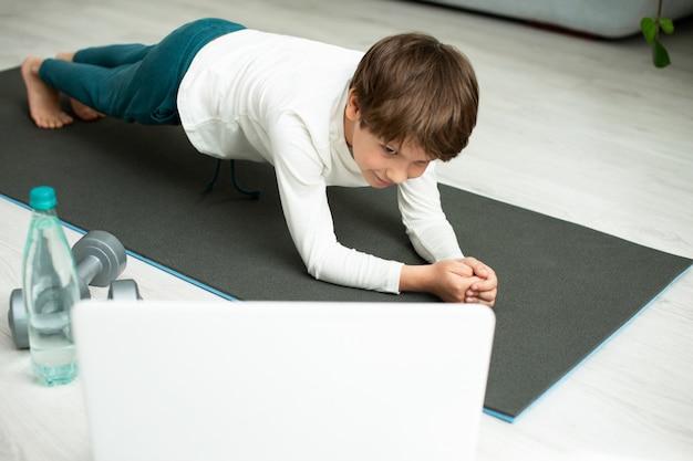 Il ragazzo fa sport online a casa. il bambino fa esercizi nella stanza. Foto Premium