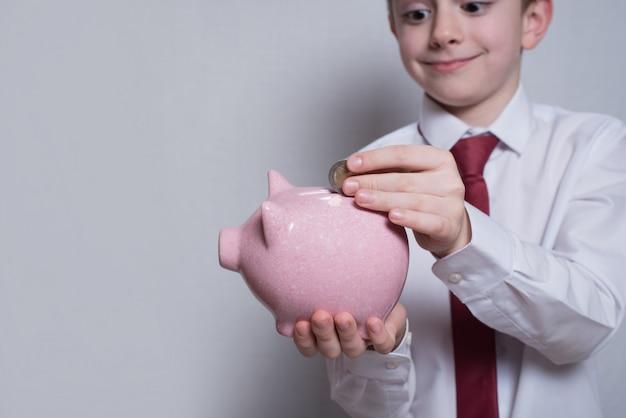 Il ragazzo felice mette una moneta in un porcellino salvadanaio rosa. Foto Premium