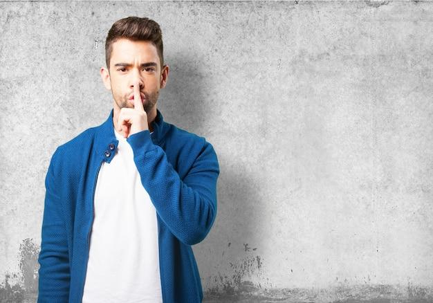 Il ragazzo in una giacca blu che chiede il silenzio Foto Gratuite