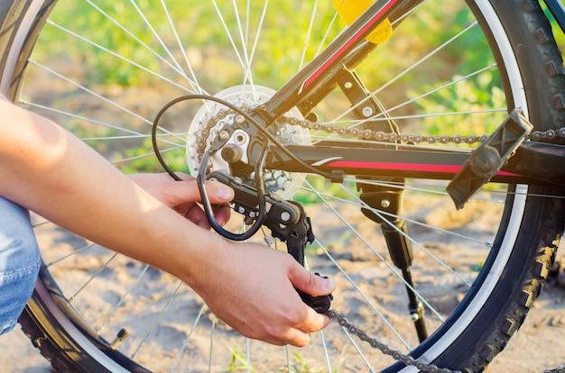 Il ragazzo ripara la bicicletta. riparazione della catena. ciclista. disatteggiamento sulla strada, viaggio, close-up. Foto Premium