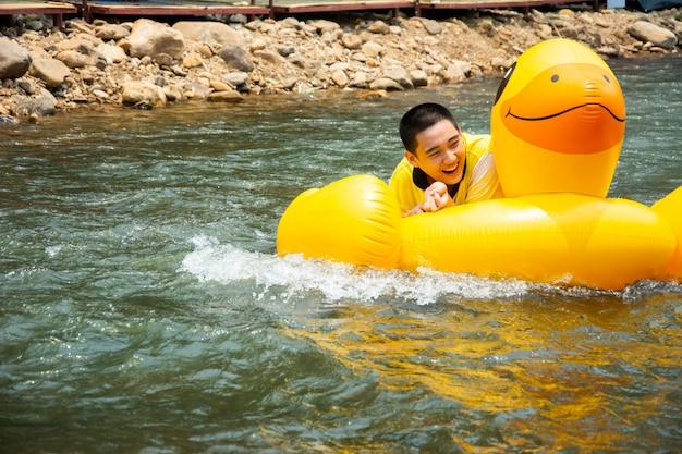 Il ragazzo si diverte e si diverte a remare a valle sul canale Foto Premium