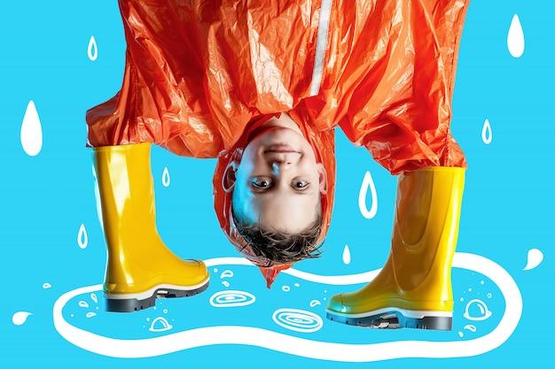 Il ragazzo sorridente in impermeabile arancio ha attaccato le sue mani in stivali di gomma su fondo blu Foto Premium