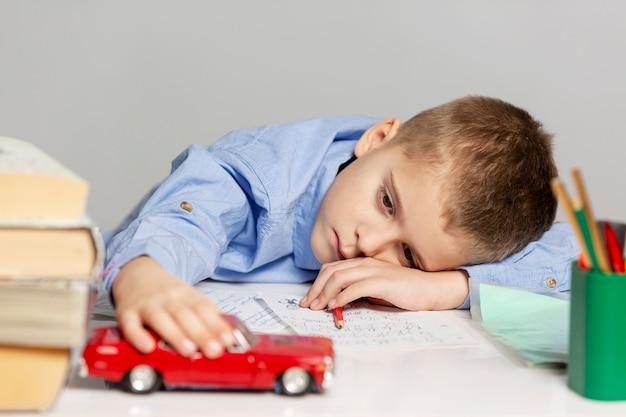 Il ragazzo stanco sveglio fa i compiti alla tavola, grigia Foto Premium