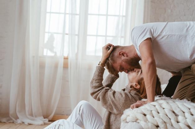 Il ragazzo sul letto bacia una donna seduta sul pavimento Foto Gratuite