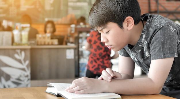 Il ragazzo sveglio asiatico ha letto i libri mentre aspettava le loro madri per comprare le bevande nel caffè. Foto Premium