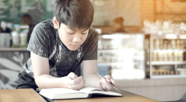 Il ragazzo sveglio asiatico ha letto i libri nel caffè. Foto Premium