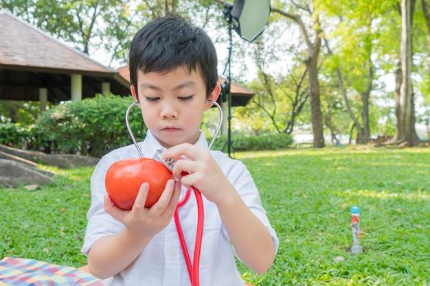 Il ragazzo usa gli stetoscopi e gioca con il simbolo del pomodoro di frutta Foto Premium
