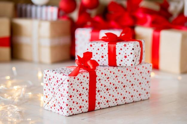 Il regalo nell'imballaggio rosso si trova su un pavimento contro lo sfondo di altri regali Foto Premium