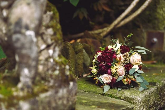 Il ricco bouquet da sposa rosso autunnale giace sulle orme di pietra Foto Gratuite