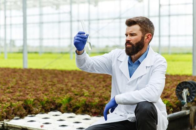 Il ricercatore prende l'acqua in una provetta seduta in una serra Foto Gratuite