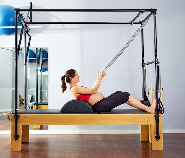 Il riformatore dei pilates della donna incinta rotola sull'esercizio Foto Premium