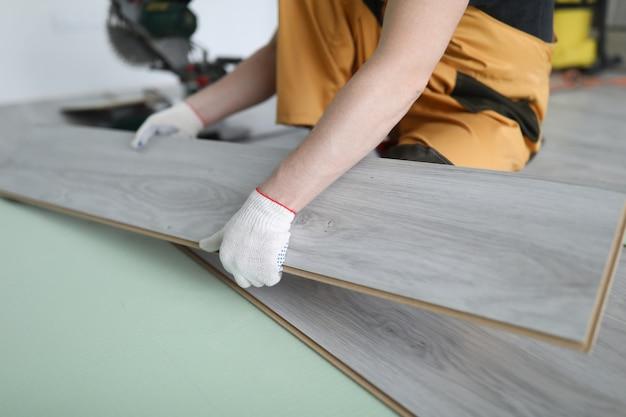 Il riparatore sostituisce l'appartamento del pavimento dei pannelli laminati Foto Premium