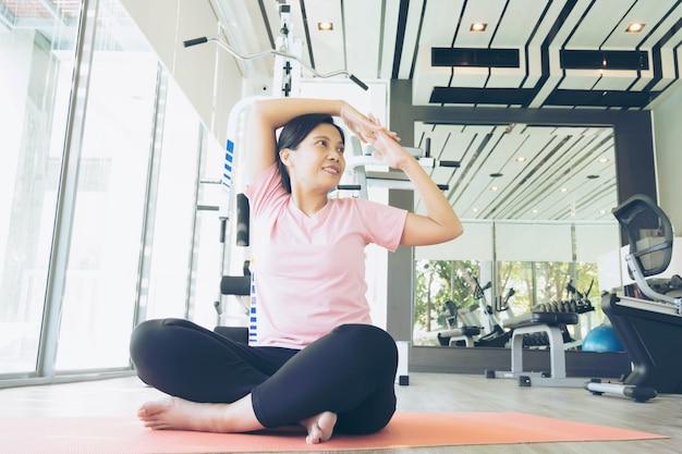 Il riscaldamento asiatico della donna di forma fisica prima di fa l'esercizio in palestra, yoga risolvente femminile di medio evo Foto Premium