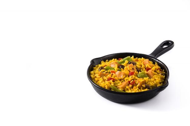 Il riso fritto con il pollo e le verdure sulla padella del ferro ha isolato lo spazio della copia Foto Premium