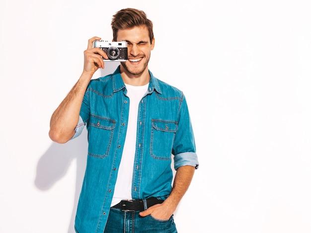 Il ritratto dei vestiti d'uso d'uso dei jeans dell'estate sorridente bello. maschera di presa maschio di modello sulla vecchia macchina fotografica d'annata della foto. Foto Gratuite