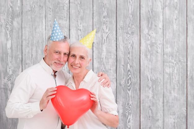 Il ritratto del cappello d'uso del compleanno delle coppie senior felici che tiene il rosso sente il pallone di forma nel fondo di legno anteriore Foto Gratuite