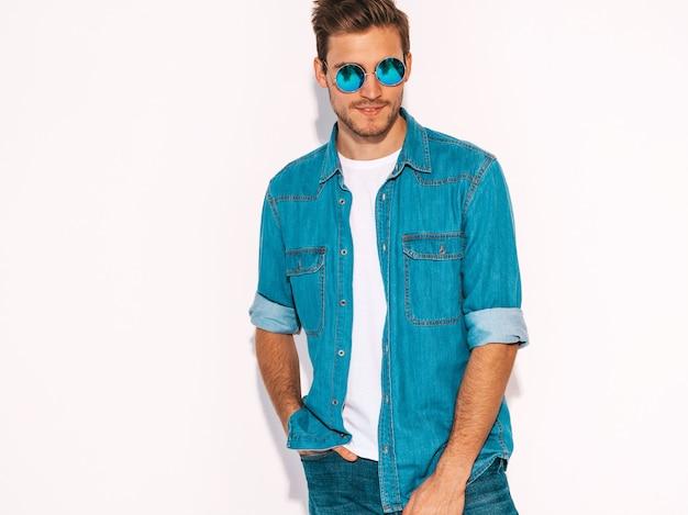 Il ritratto del modello alla moda sorridente bello del giovane si è vestito in vestiti dei jeans. moda uomo che indossa occhiali da sole. Foto Gratuite
