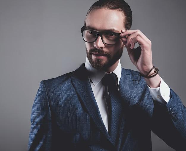 Il ritratto del modello bello dell'uomo d'affari di modo si è vestito in vestito blu elegante con i vetri Foto Gratuite