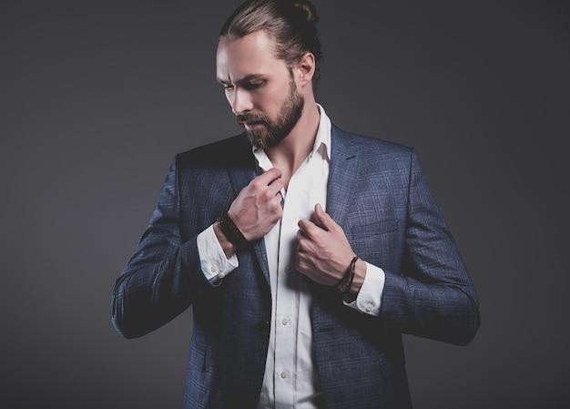 Il ritratto del modello dell'uomo d'affari alla moda dei pantaloni a vita bassa alla moda bello si è vestito in vestito blu elegante che posa sul gray Foto Gratuite