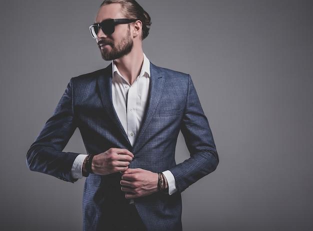 Il ritratto del modello dell'uomo d'affari alla moda dei pantaloni a vita bassa alla moda bello si è vestito in vestito blu elegante in occhiali da sole che posano sul gray Foto Gratuite