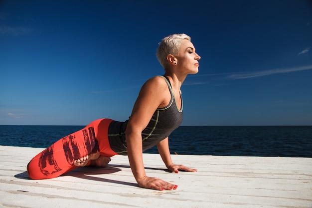 Il ritratto del primo piano della donna bionda adulta con taglio di capelli corto pratica l'yoga Foto Premium