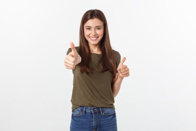 Il ritratto del primo piano di bella giovane donna che mostra i pollici aumenta il segno Foto Premium