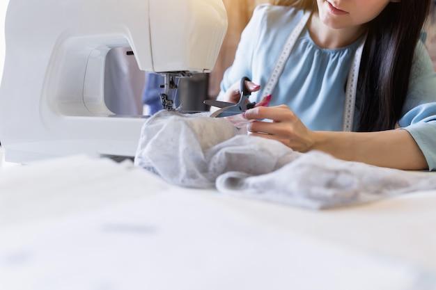 Il ritratto del primo piano di giovane cucitrice o sarta indiana indiana cuce sulla macchina per cucire nel suo proprio posto di lavoro. Foto Premium