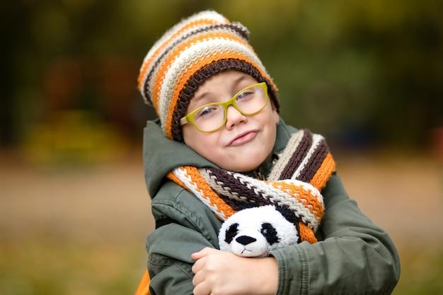 Il ritratto del ragazzo carino con gli occhiali e caldo cappello a maglia e sciarpa con il suo panda giocattolo nel parco in autunno Foto Premium