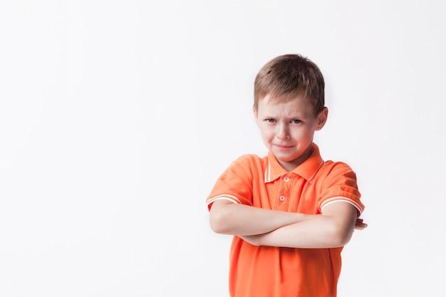 Il ritratto del ragazzo innocente con il braccio ha attraversato contro la parete bianca Foto Gratuite